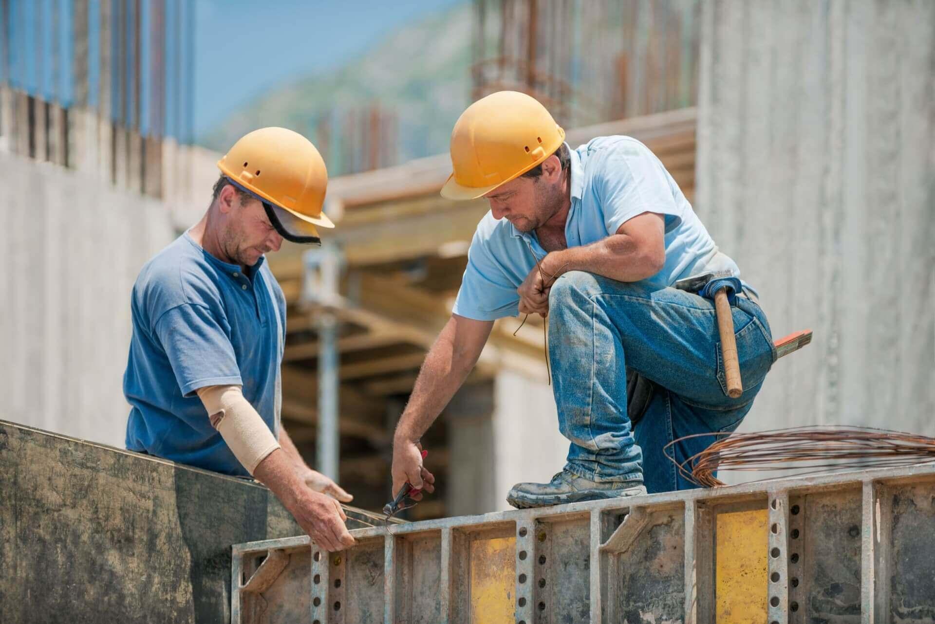 Dwóch pracowników budowlanych montujących betonowe ramy szalunkowe
